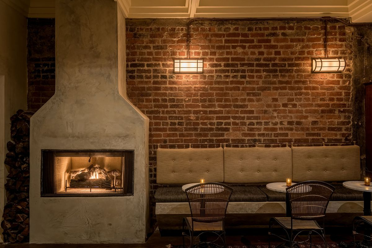A small indoor fireplace rolls next to a cushioned seat.