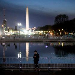 Dana Tatnell, a resident of Washington, D.C., pauses during a run near the U.S. Capitol on Thursday, Jan. 19, 2017.