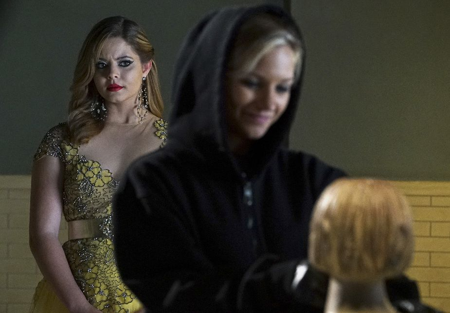 Charlotte DiLaurentis in black hoodie combs hair on a mannequin while her sister Alison watches behind her in a yellow dress.