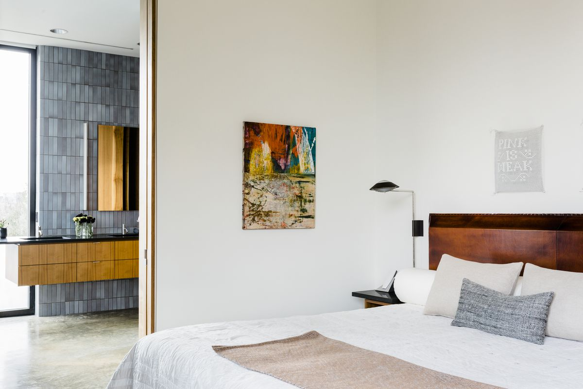 In the bedroom, art decorates the walls. Through the door, you can see the light blue tile of the master bathroom.