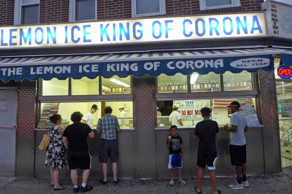 A broad window with people lined up to buy ices.