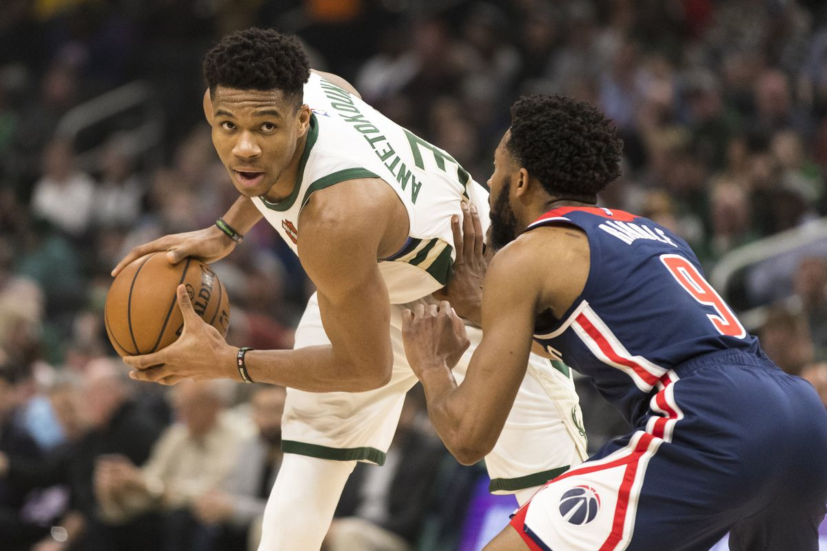 Milwaukee Bucks forward Giannis Antetokounmpo holds the ball away from Washington Wizards guard Chasson Randle during the second quarter at Fiserv Forum.