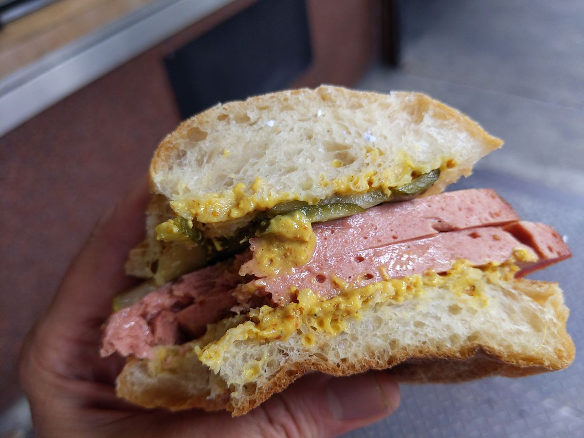 A smallish round bun with two thick slices of luncheon meat on it, held by a hand.