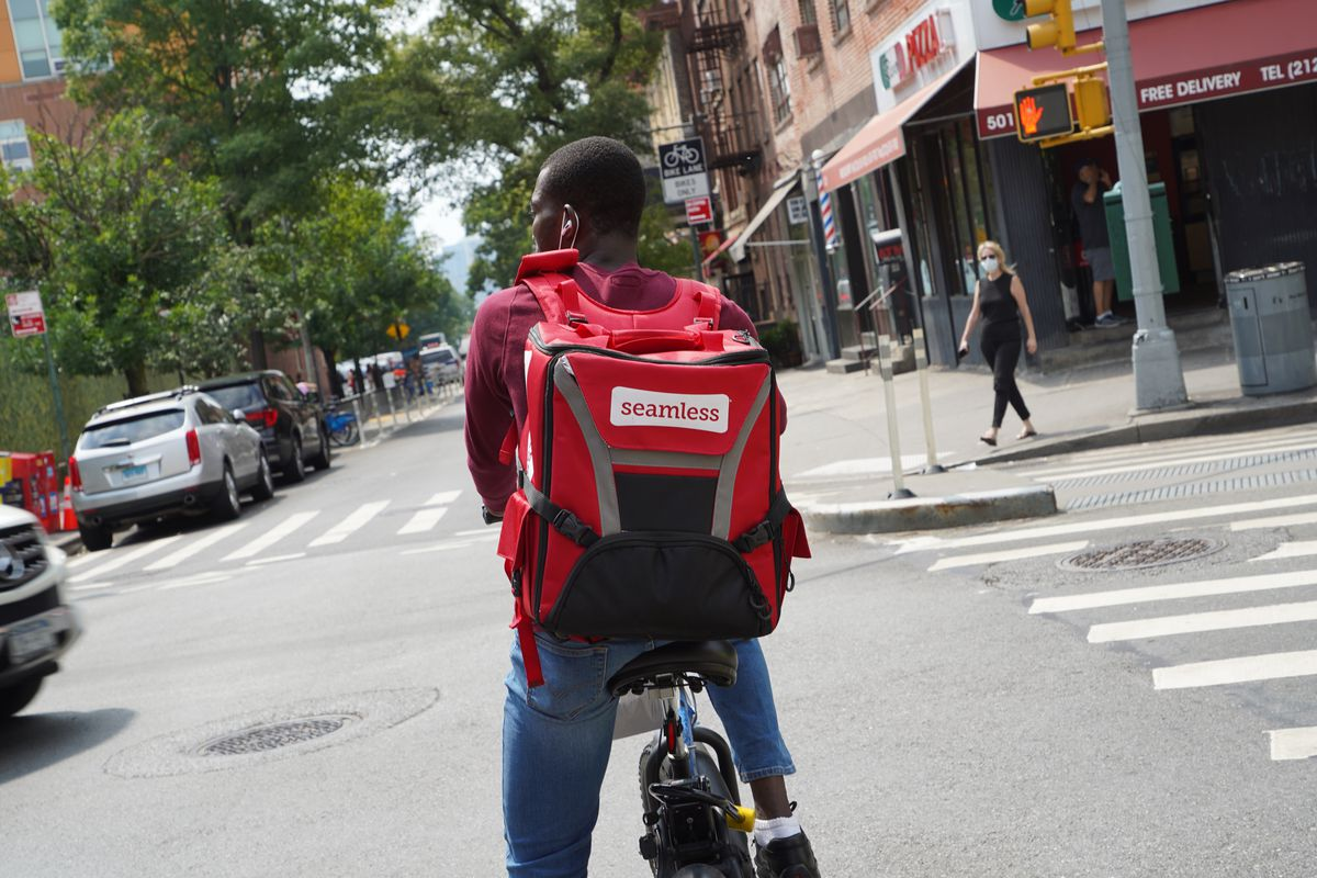 A food delivery worker from Seamless waits on his bicycle for cars to pass on a street in the West Village during Phase 4 of re-opening following restrictions imposed to curb the coronavirus pandemic on August 6, 2020 in New York, New York.