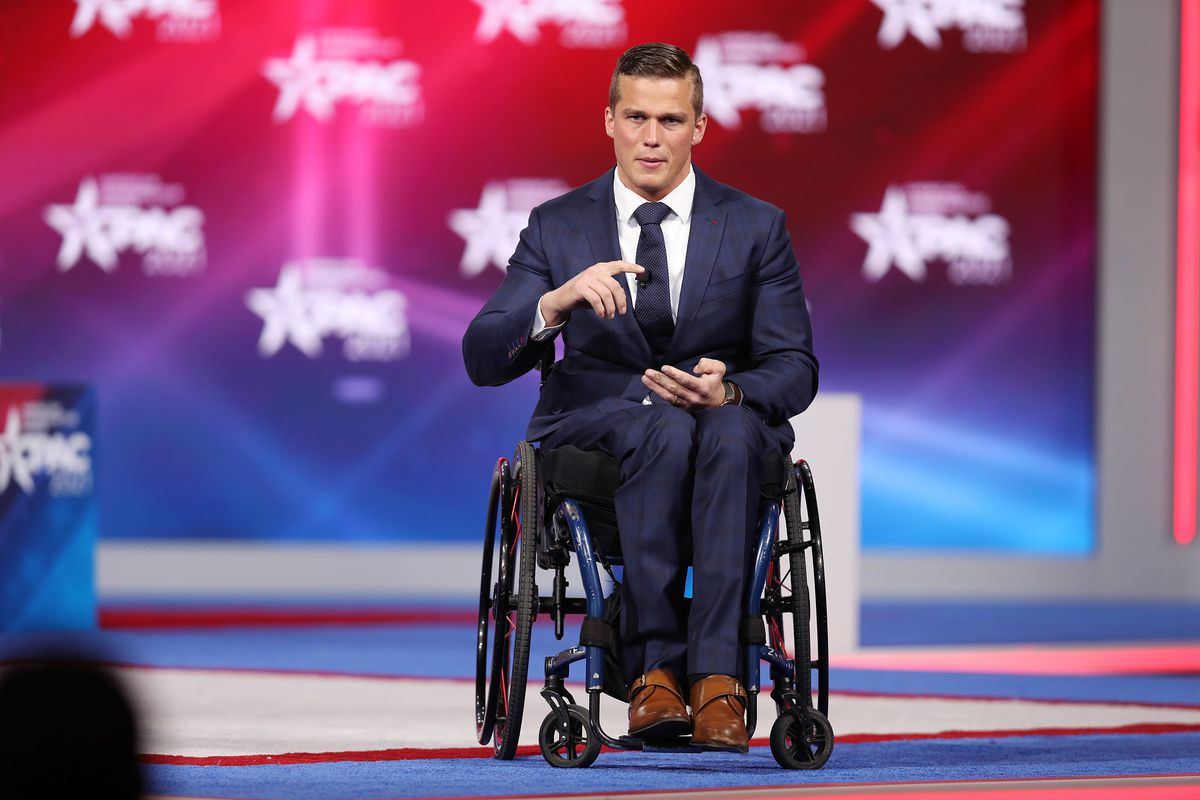 Cawthorn sits in a wheelchair, wearing a navy suit and tie and brown shoes, speaking with a red-and-blue backdrop behind him.