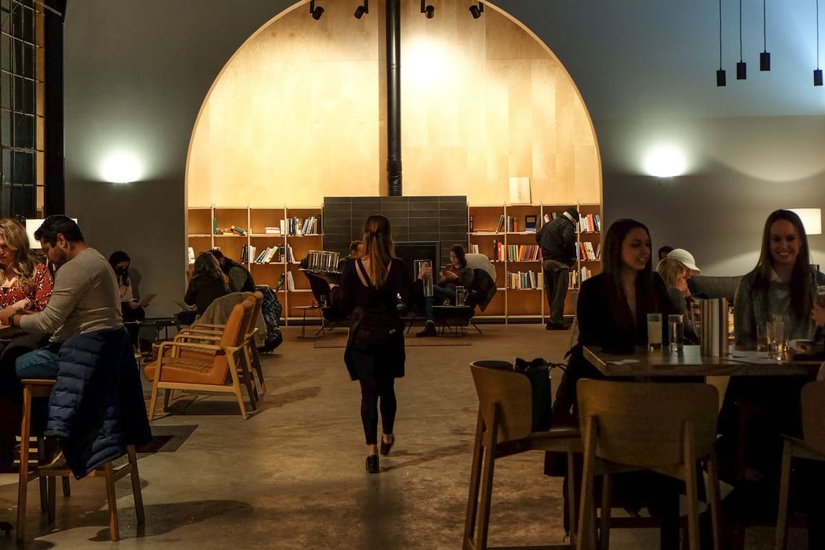 A dimly lit room with a white archway shows a server in all black, carrying trays of drinks. On either side of her, spaced well-apart, are tables of people enjoying drinks.