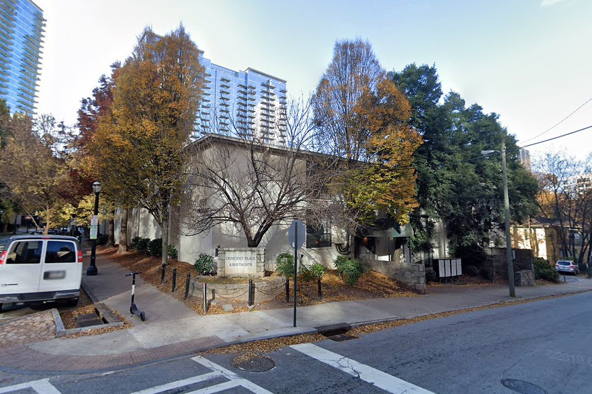 A picture of low-rise apartments surrounded by small street trees and beneath skyscrapers in the background.