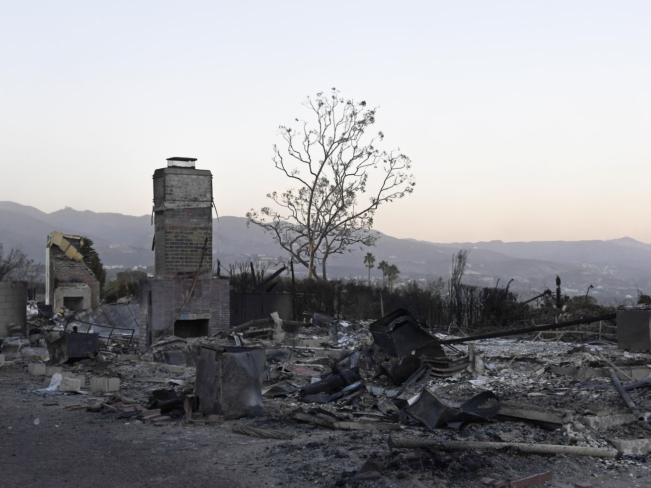 Destroyed houses are seen with the Santa Monica Mountains in the background on Monday in Malibu.