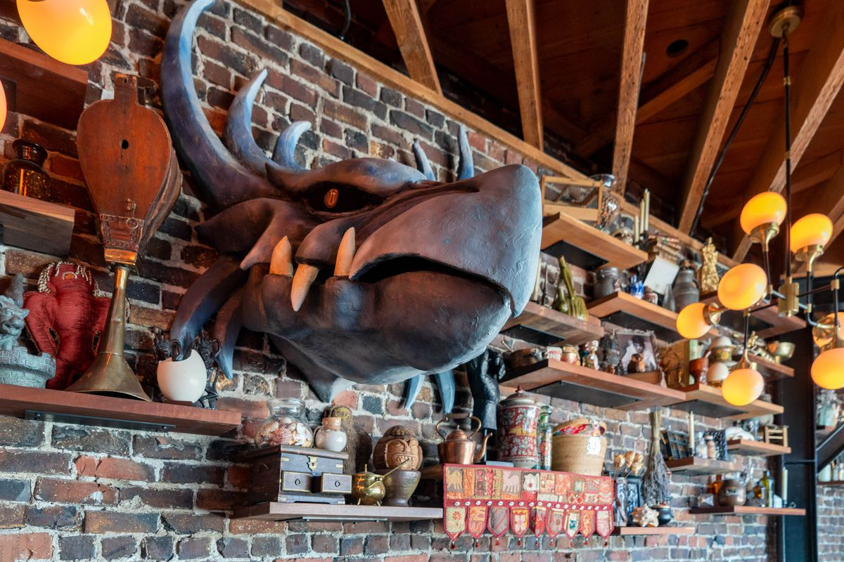 A large plaster dragon's head sticks out from a brick wall, surrounded by various old artifacts and hanging overhead orange lights.
