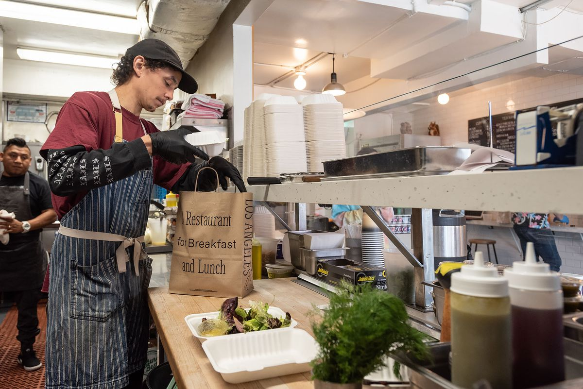 Worker packs takeout order at Sqirl in March, 2020