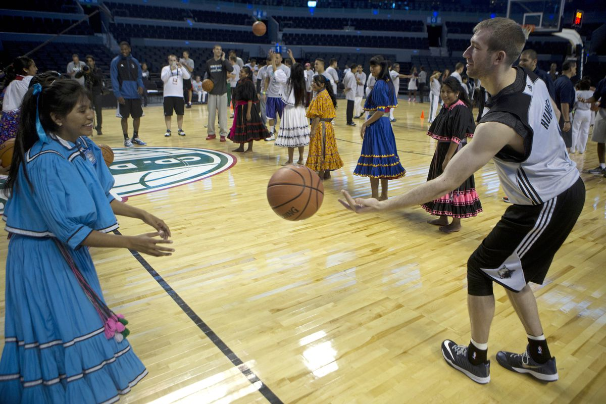 FILE: Robbie Hummel of the Minnesota Timberwolves passes the ball to a player from the Tarahumara Indigenous basketball team, from Mexico's Chihuahua state, at the Arena Ciudad de Mexico in Mexico City, Tuesday, Nov. 11, 2014.