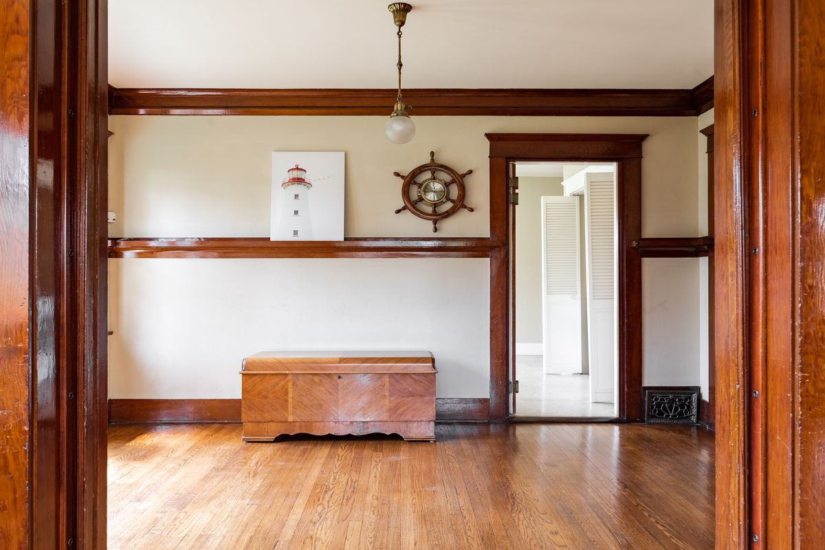 A room with wood floors and a captain's wheel mounted on the wall