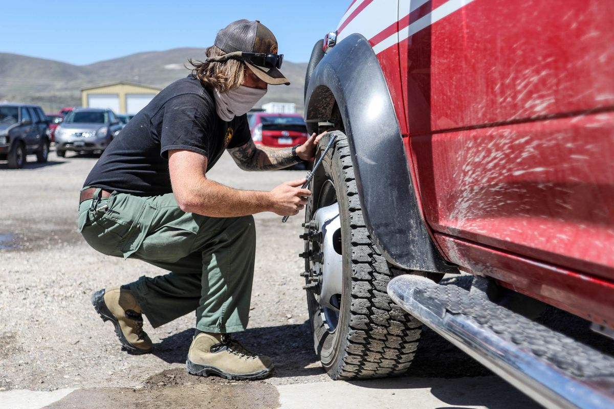 Unified Fire Authority wildland firefighter Patrick Nordstrom checks the lugnuts on a fire brush truck at Station 127 at Camp Williams on Thursday April 29, 2021. Nordstrom stayed at the station while the majority of his colleague participated in training for the upcoming wildfire season.