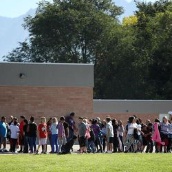 Students line up to go back inside after recess at Westbrook Elementary School in Taylorsville on Thursday, Sept. 11, 2014. Earlier, a teacher accidentally shot herself in the leg, while alone in a faculty bathroom, shortly before school started.