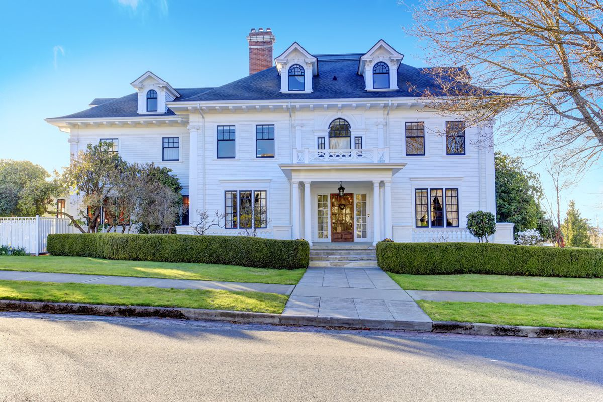 Large white southern home with large green front yard and white columns.