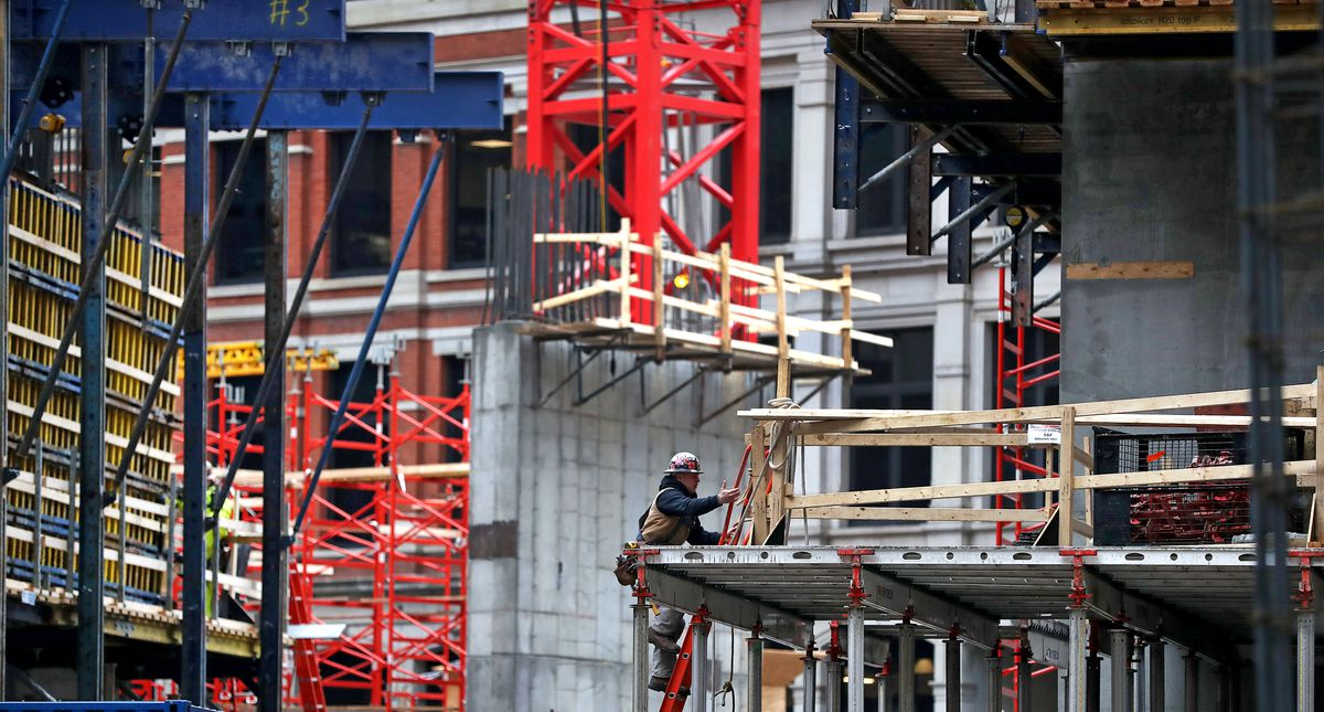 A construction worker working with a wood frame of a building several stories up.