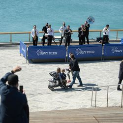 A band plays as people walk around Navy Pier on its reopening day, Friday morning, April 30, 2021. Navy Pier was closed in 2020 due to the COVID-19 pandemic.