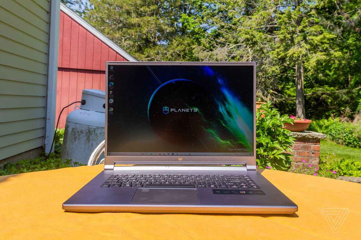 The Acer Predator Triton 500 SE on a yellow tablecloth in a garden, open. The screen displays the Planet9 logo on a dark background.