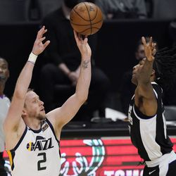 Utah Jazz guard Joe Ingles, left, shoots as Los Angeles Clippers guard Terance Mann defends during the second half of Game 3 of a second-round NBA basketball playoff series Saturday, June 12, 2021, in Los Angeles.
