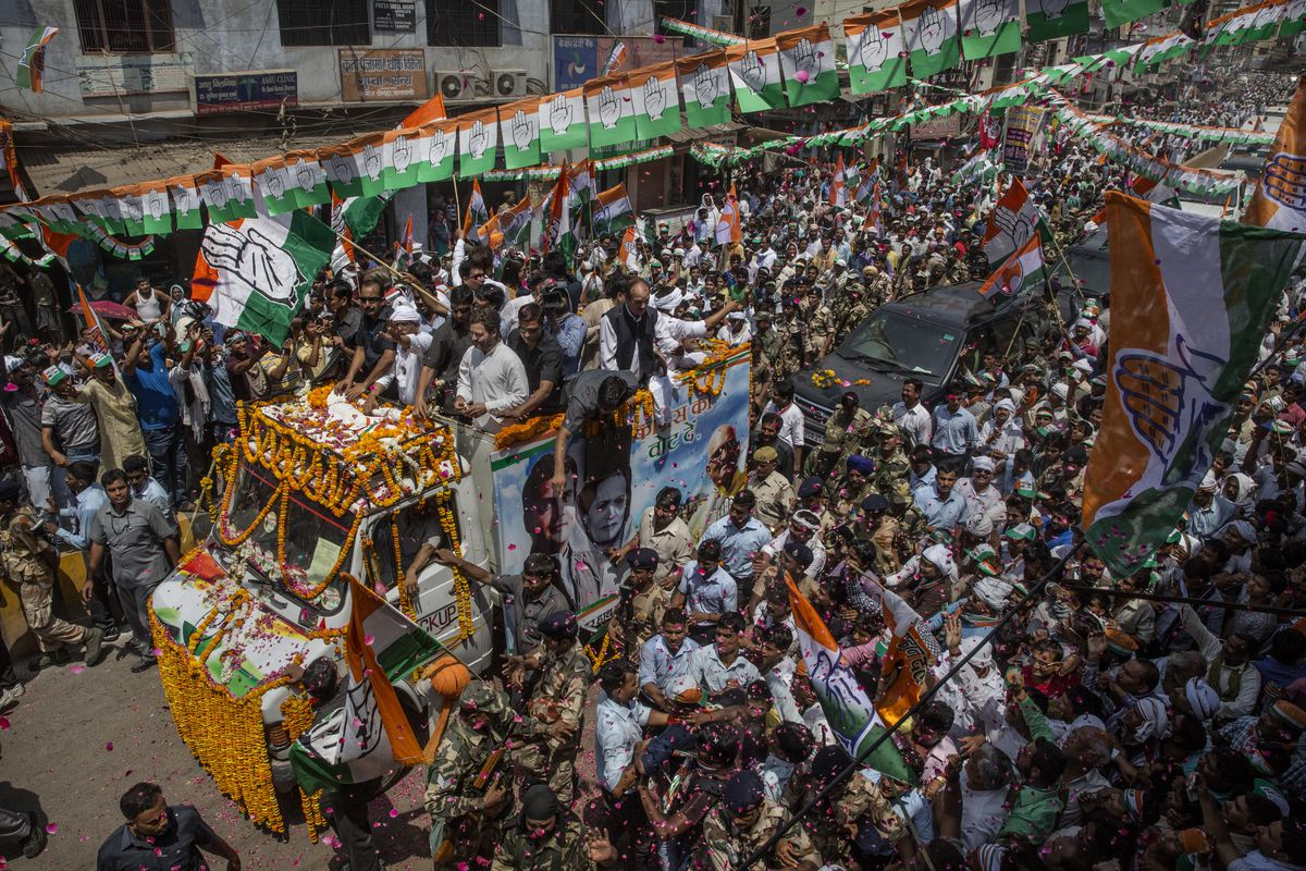A political rally in India featuring a large crowd gathered around a heavily decorated bus.