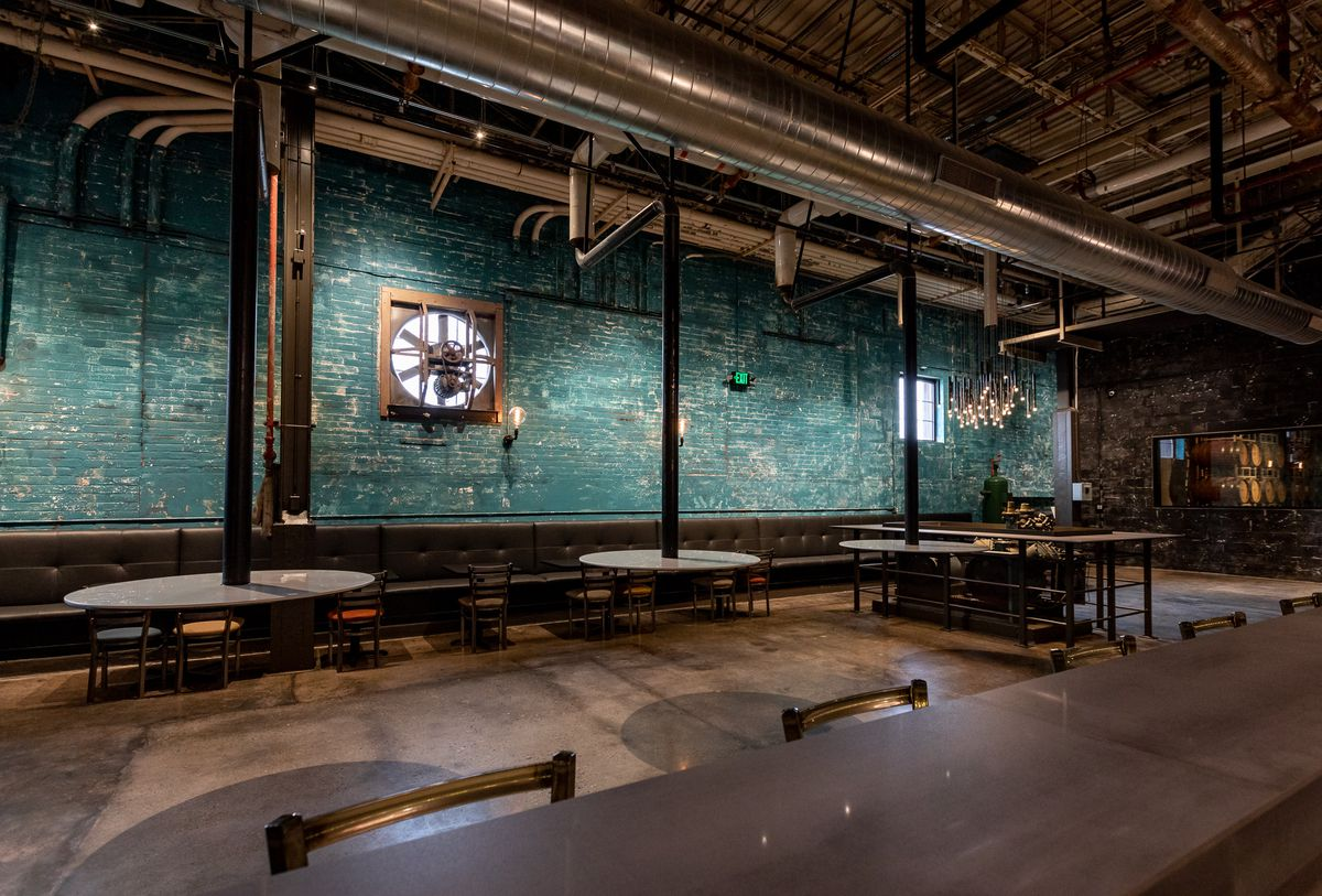 The industrial interior at Detroit Vineyards features blue walls and floating tables.