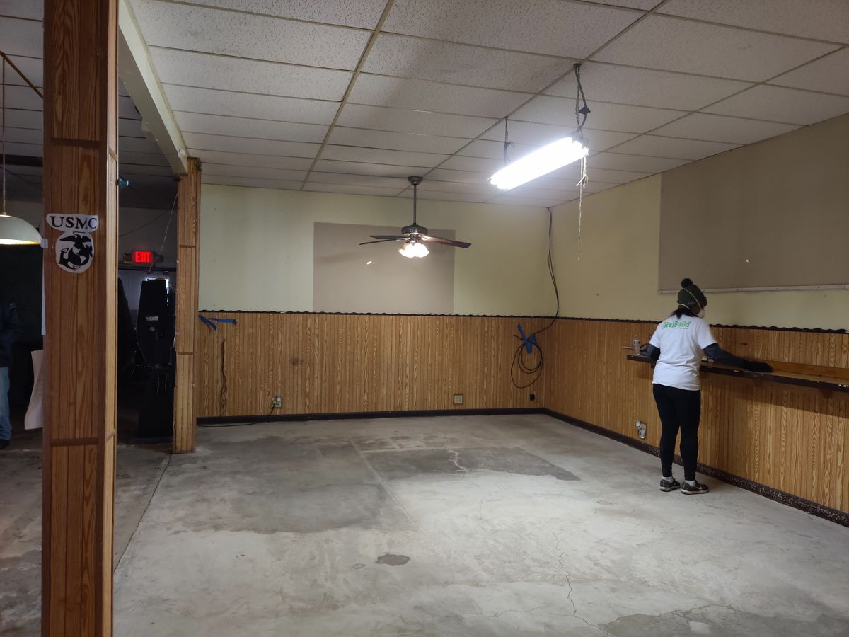 A woman cleans the main gathering area at Montford Point Marines Association, Inc. Chicago Chapter No. 2. Volunteers with the chapter in partnership with Rebuilding Together Metro Chicago and Sears spent Veterans Day renovating the center.