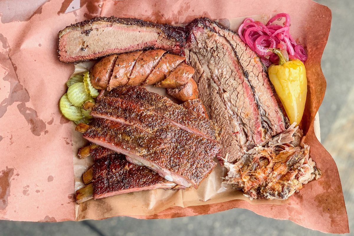 Moo's craft barbecue sits on a pink paper tray.