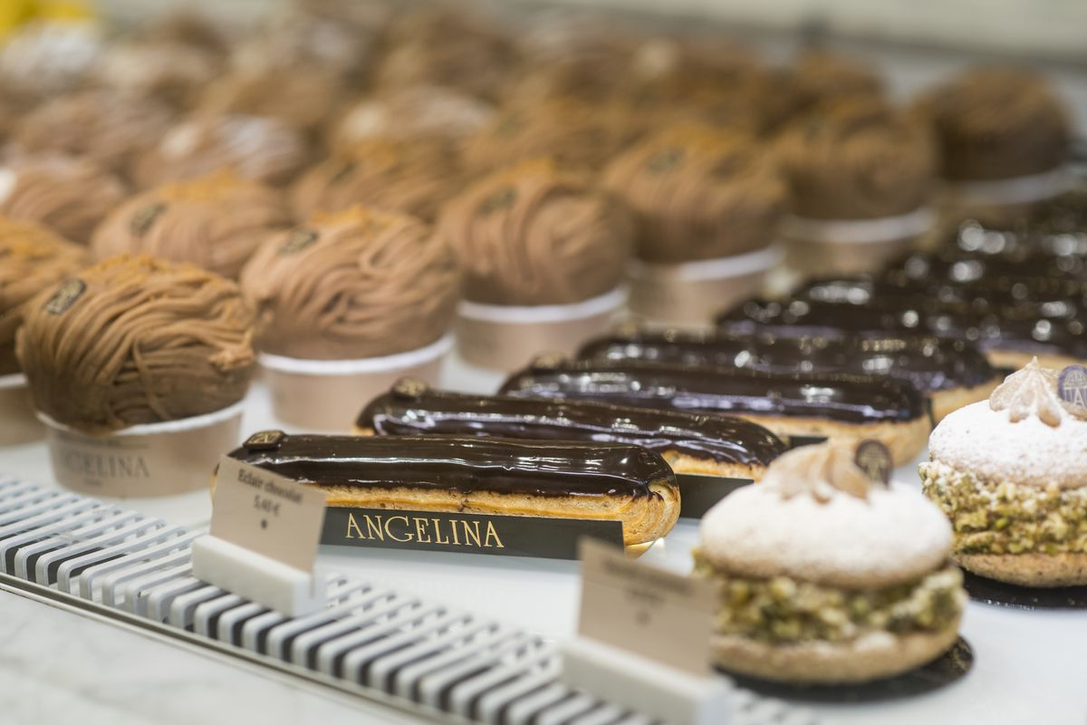 A row of pastries can be seen sitting on a shelf behind a glass wall