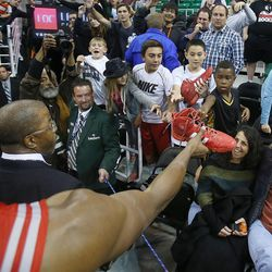 Houston's Dwight Howard hands one of his shoes to a young fan after the game as Houston defeats the Jazz Saturday, Nov. 2, 2013 in Energy 104-93.