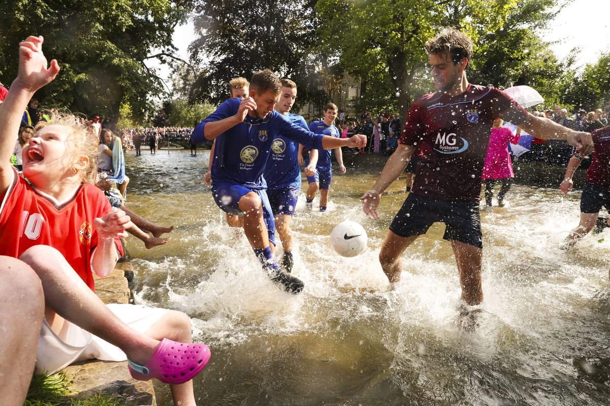 August 27: Players from Bourton Rovers compete against each other during the annual Bourton-on-the-Water Football Match played on the River Windrush in Bourton-on-the-Water, England. (Catherine Ivill/Getty Images)
