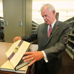 LDS Church Historian and Recorder Elder Steven E. Snow, shows a few of the pages of the new volume as the LDS Church, in cooperation with the Community of Christ announces the release of the printers manuscript of the the Book of Mormon, during a press conference Tuesday, Aug. 4, 2015, at the LDS Church's History library in Salt Lake City.