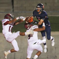 Brighton's Simi Fehoko out-jumps Herriman's Noah Vaea and Tanner Rosenhan for the ball to score a touchdown as Brighton and Herriman play Friday, Aug. 21, 2015, at Brighton. Brighton won 23-14.
