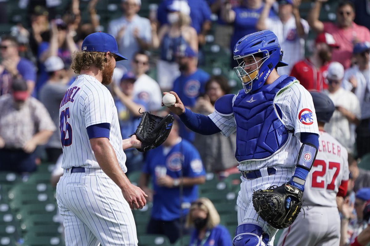 Cubs catcher P.J. Higgins congratulates closer Craig Kimbrel after Kimbrel struck out the side in the ninth inning of the Cubs' 5-2 victory over the Nationals at Wrigley Field.
