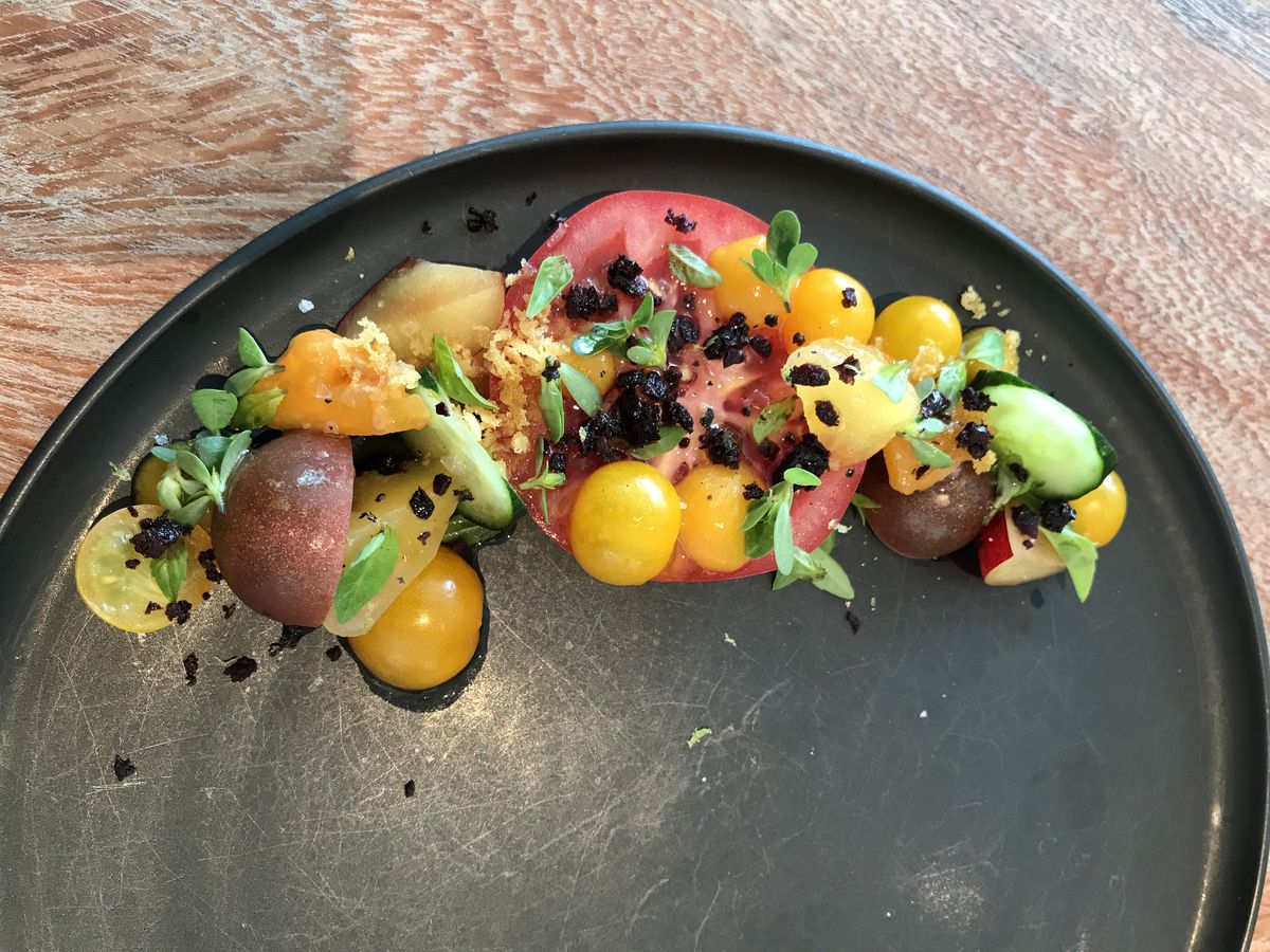 From above, an artistically-presented tomato salad dish with various herbs and garnishes, geometrically sequestered to one edge of a round dish.