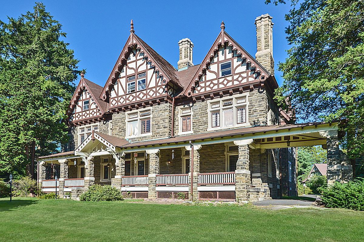 An elegant stone Tudor mansion with a large wrap-around porch