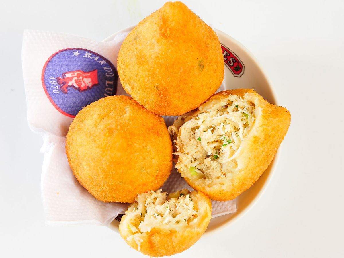 A bowl of chicken fritters, two whole and one split open, on a napkin bearing the Bar do LuizFernandes on a blank background.