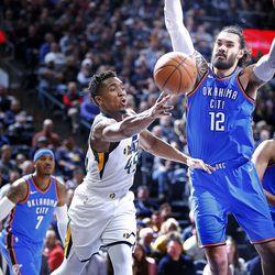 Utah Jazz guard Donovan Mitchell passes around Oklahoma City Thunder center Steven Adams during NBA basketball in Salt Lake City on Saturday, Dec. 23, 2017.