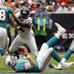 Miami Dolphins quarterback Ryan Tannehill (17) trips and falls to the ground after taking the snap as center Richie Incognito (68) blocks Houston Texans defensive end Antonio Smith (94) in the second quarter of an NFL football game, Sunday, Sept. 9, 2012, in Houston.