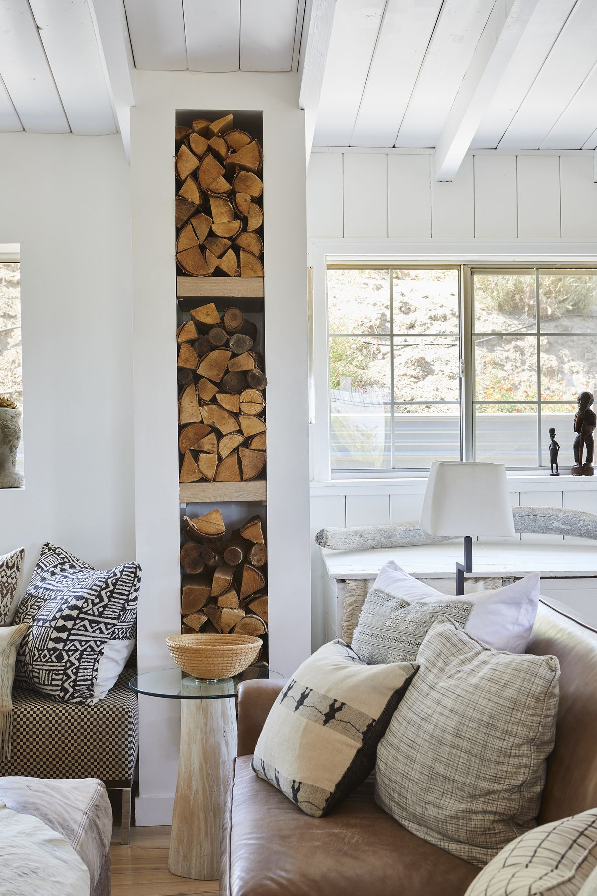 A tall, white wood-storage system separates white paneled walls and smooth drywall. Stacks of firewood fill the shelves.