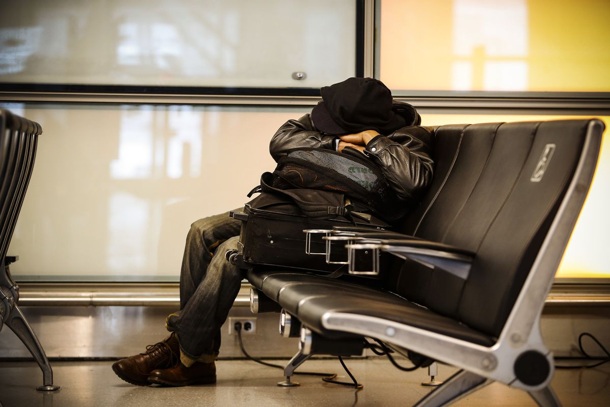 A passenger naps in Logan Airport in Boston, Massachusetts where a nor'easter storm cancelled the majority of flights, on March 13, 2018.