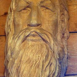 In this April 11, 2012 photo, a face, carved by local woodworking artist Phil Marshall in 1992 while studying under the late German woodcarving master Georg Kielhofer, hangs in his sauna at his home outside of Fairbanks, Alaska.   Marshall is the creator of distinctive, one-of-a-kind wooden furniture.