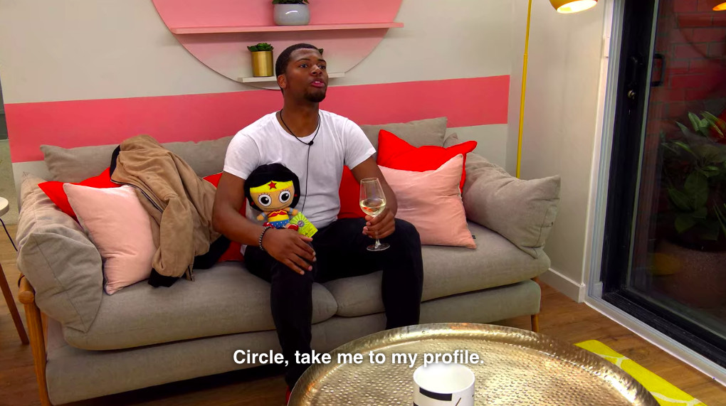 A reality show character The Circle holds a stuffed doll, a glass of wine and asks to see his profile.