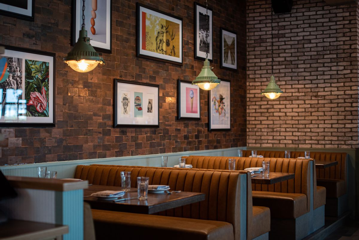 Leather booths and art and brick at a new restaurant.