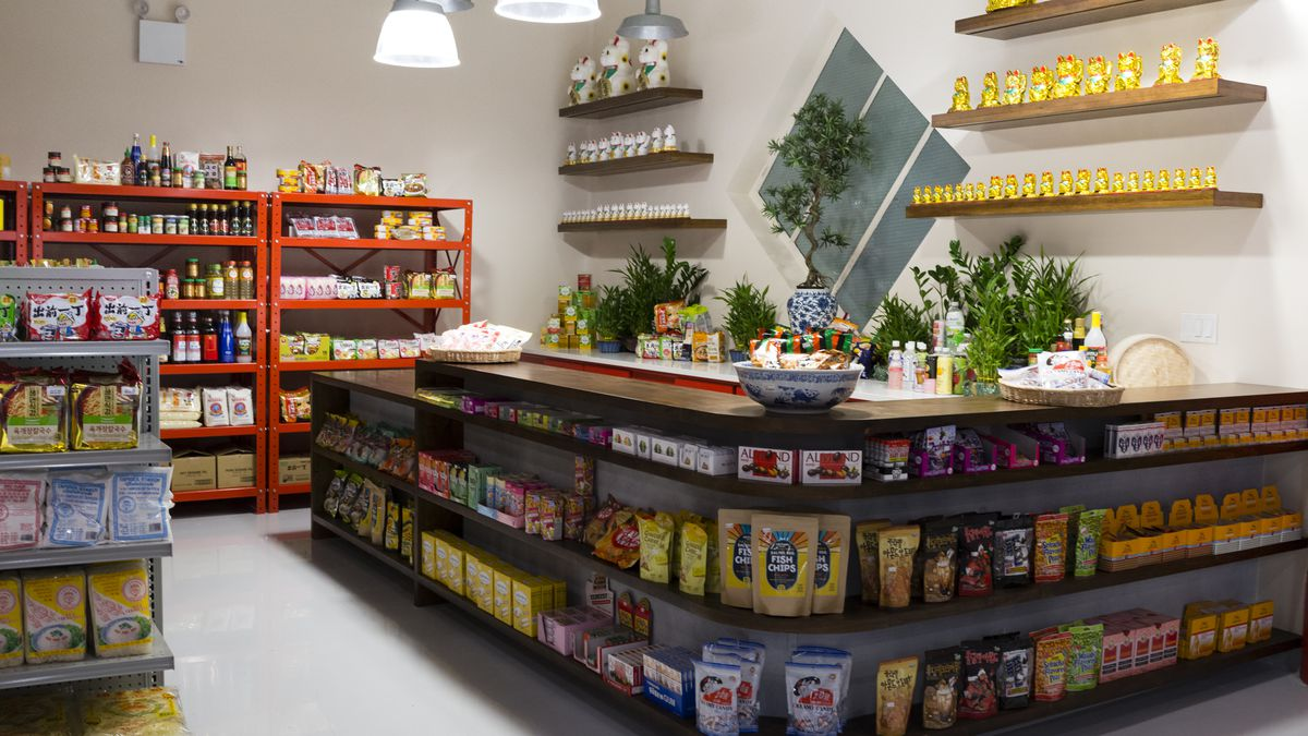The inside of a grocery store with stocked shelves and a round counter where the cash register is placed