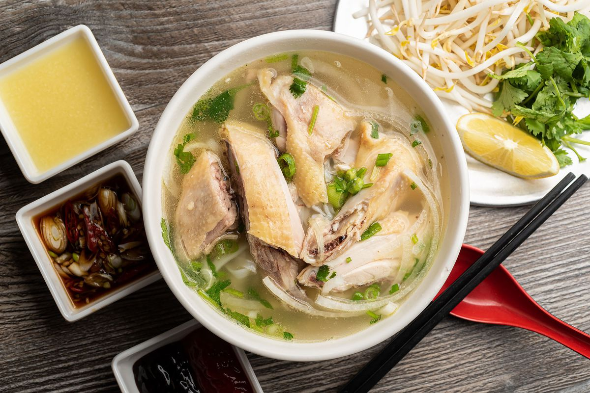 Bowl of chicken pho with sauces, and toppings.