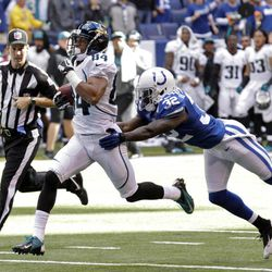 Jacksonville Jaguars wide receiver Cecil Shorts (84) breaks the tackle of Indianapolis Colts defensive back Cassius Vaughn on his way to 80-yard touchdown in the final minute of an NFL football game in Indianapolis, Sunday, Sept. 23, 2012. The Jaguars defeated the Colts 22-17.