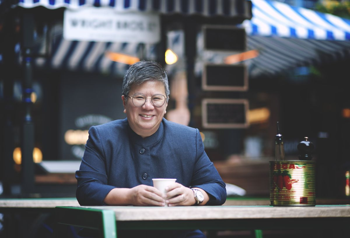 Ellen Chew, restaurateur, Chew On This, sits a table smiling with a takeaway coffee cup