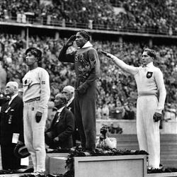 America's Jesse Owens, center, salutes during the presentation of his gold medal for the long jump on Aug. 11, 1936, after defeating Nazi Germany's Lutz Long, right, during the 1936 Summer Olympics in Berlin. Naoto Tajima of Japan, left,  placed third.