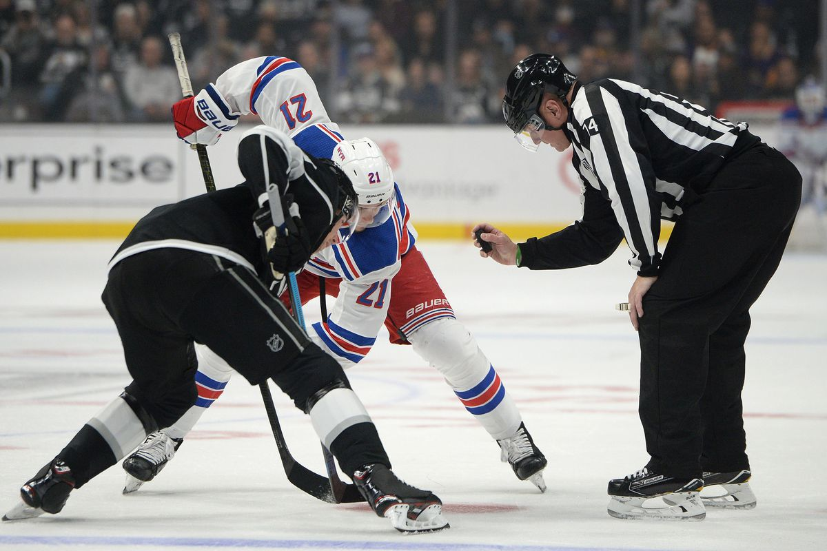 Oct 28, 2018; Los Angeles, CA, USA; New York Rangers center Brett Howden (21) and Los Angeles Kings center Adrian Kempe (left) await referee Dennis LaRue (14) during a face-off during the first period at Staples Center.