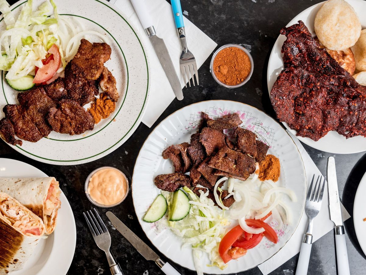A spread of Hausa suya, grilled beef spiced with yaji, served on white plates with a salad of lettuce, tomato, and raw onion.